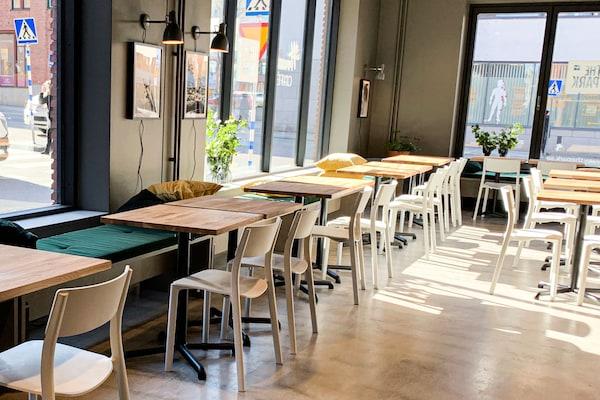 Cafédelen är ljus och luftig. Längs med ena väggen finns en platsbyggd soffa, framför står många fyrkantiga småbord.