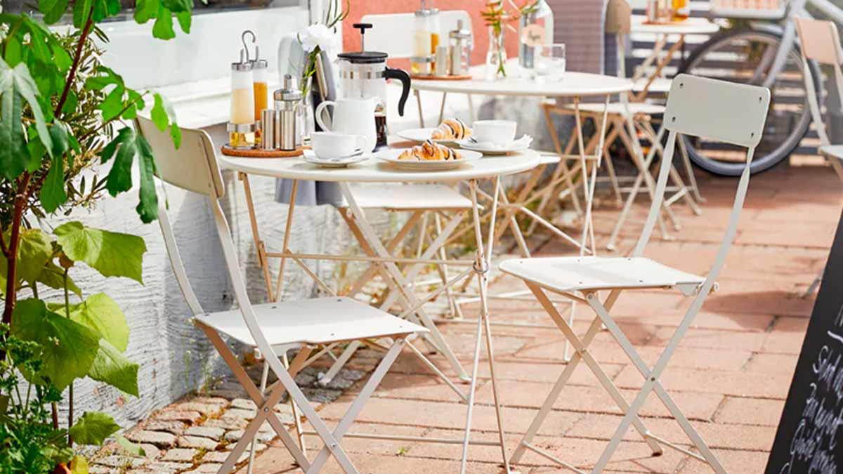 Caffè all'aperto con tavoli e sedie da giardino TUNHOLMEN in grigio. Diversi tavoli e sedie sono impilati o ripiegati – IKEA