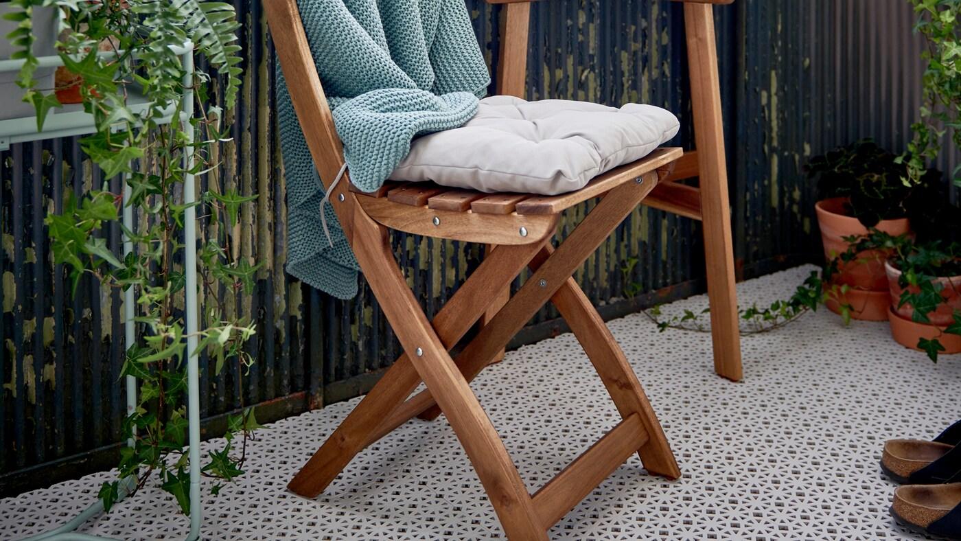 Caillebotis ALTAPPEN posé sur le sol d'un balcon avec une chaise pliante ASKHOLMEN, une table et des plantes.
