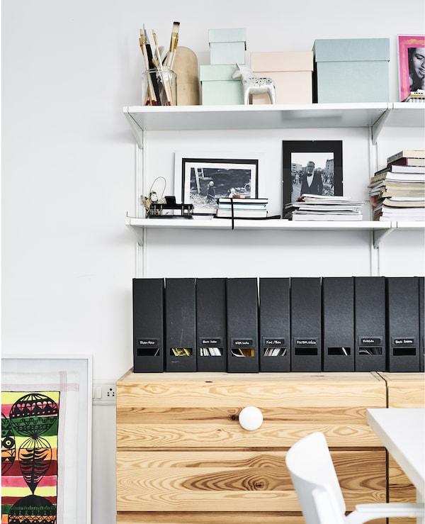 Caixas de arquivo e prateleiras por cima de uma cómoda de madeira