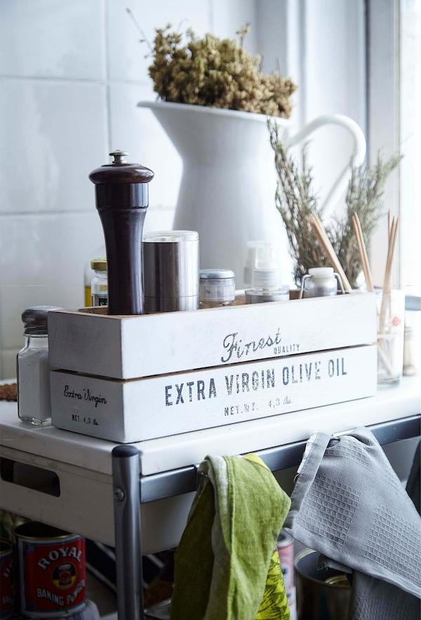 Caja de madera para almacenaje en una cocina con un molinillo de pimienta y una jarra metálica para la leche.