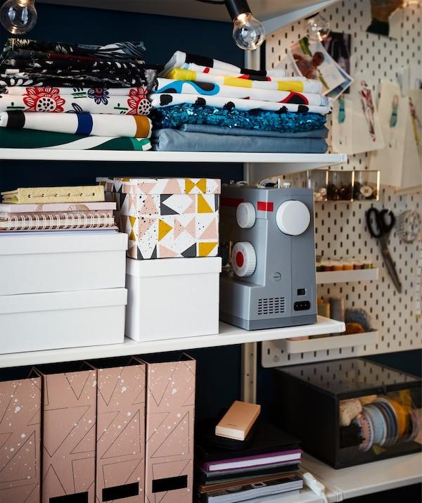 Cajas de almacenaje, archivadores de revistas, telas y una máquina de coser en estanterías.