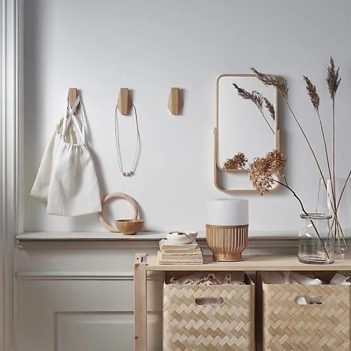 Cajas de almacenamiento de bambú en un mueble de madera, un espejo y ganchos de bambú en una pared blanca.