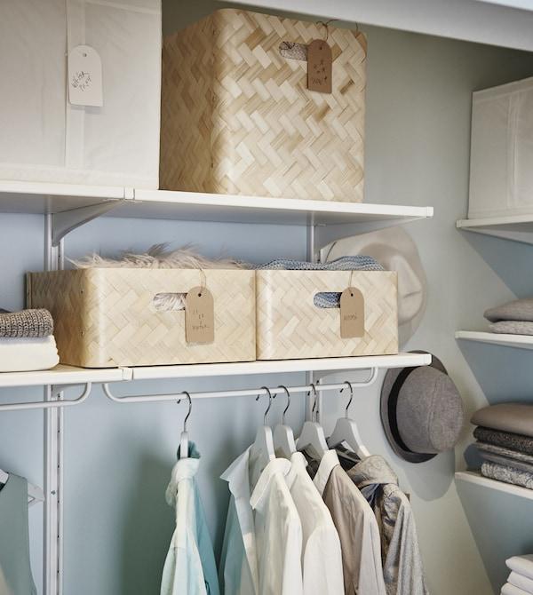 Cajas de bambú BULLIG en dos tamaños diferentes en estantes ajustables con barra para colgar ropa debajo.