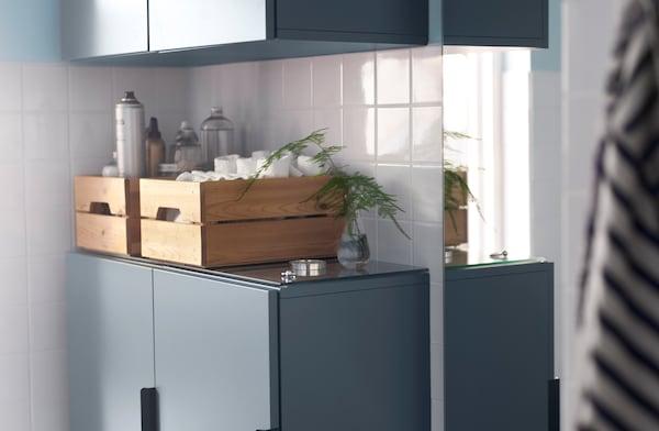 Cajas de madera sobre armarios azules ayudan a organizar los elementos básicos del baño.