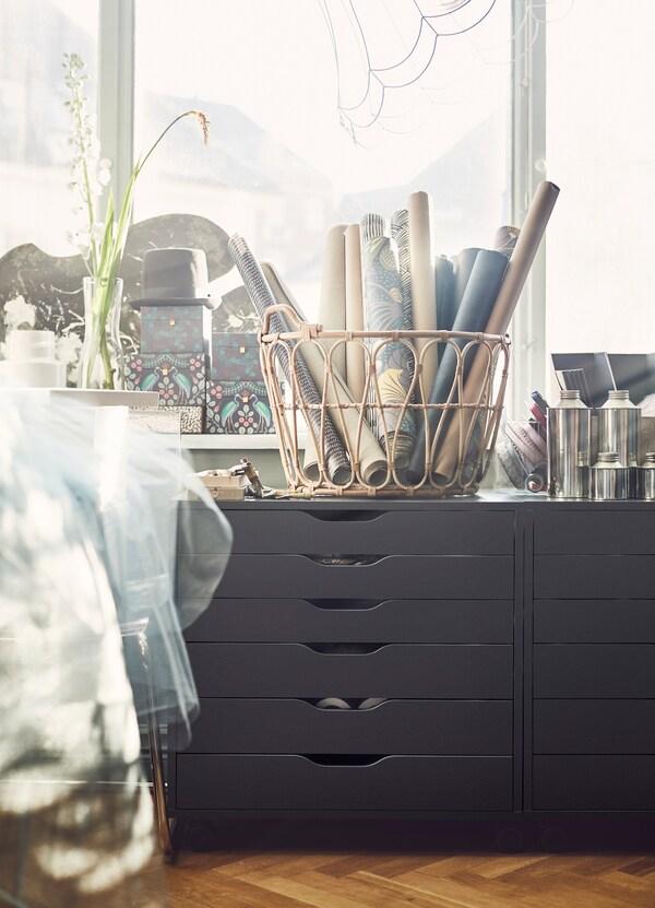 Cajonera negra ALEX con seis baldas rectangulares y cestas de ratán con rollos de tela.
