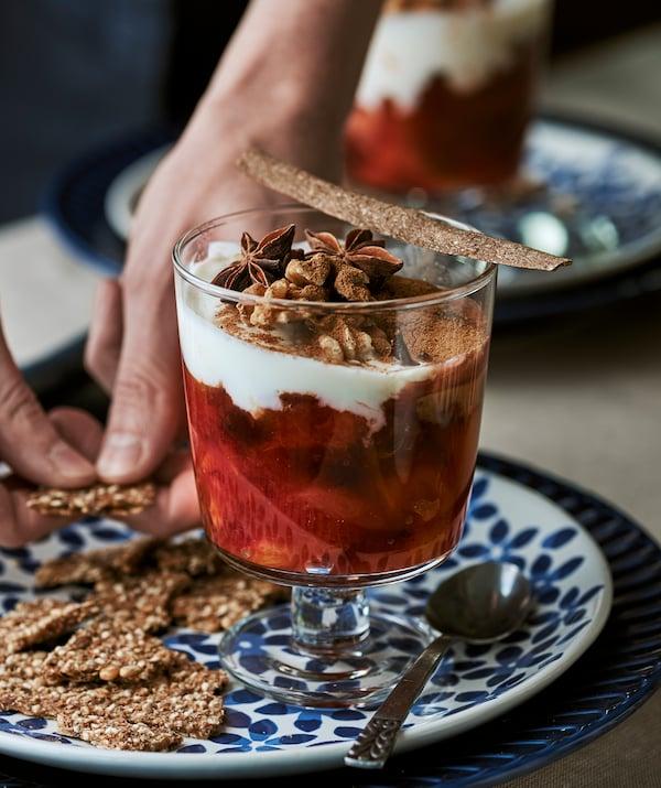 Calice in vetro con frutta cotta e yogurt, su un piatto blu con fantasia a fiori - IKEA