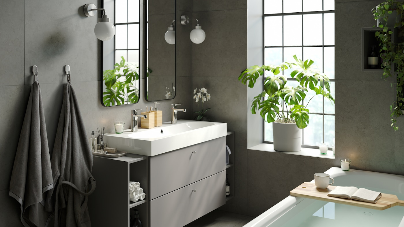 Calm relaxing bathroom with modern elegant bathtub, a wide single sink with storage, double mirrors and indoor green plants.