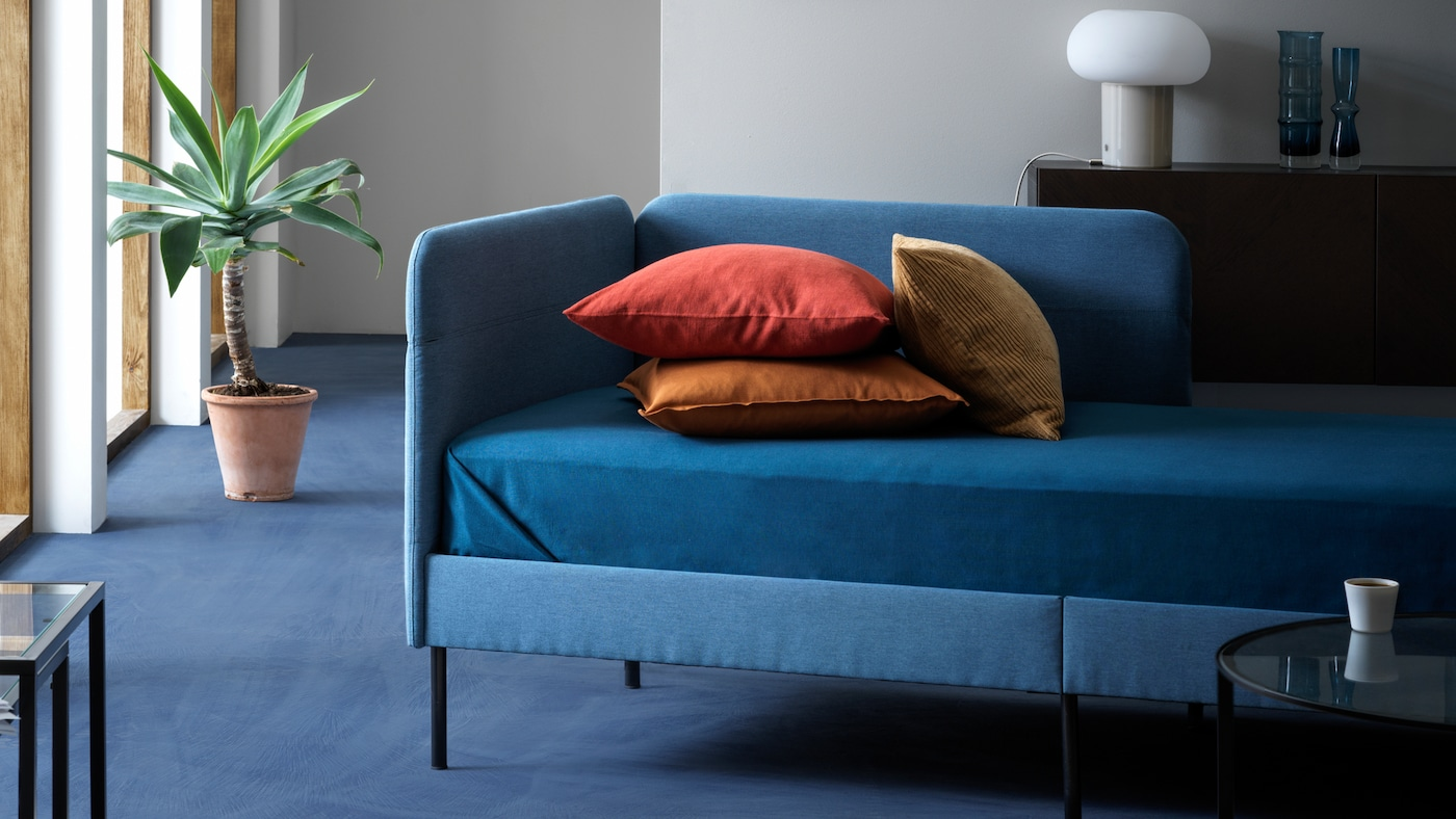 Čalúnený rám postele BLÅKULLEN a na ňom vankúše zemitých farieb v dobre osvetlenej obývacej izbe.
