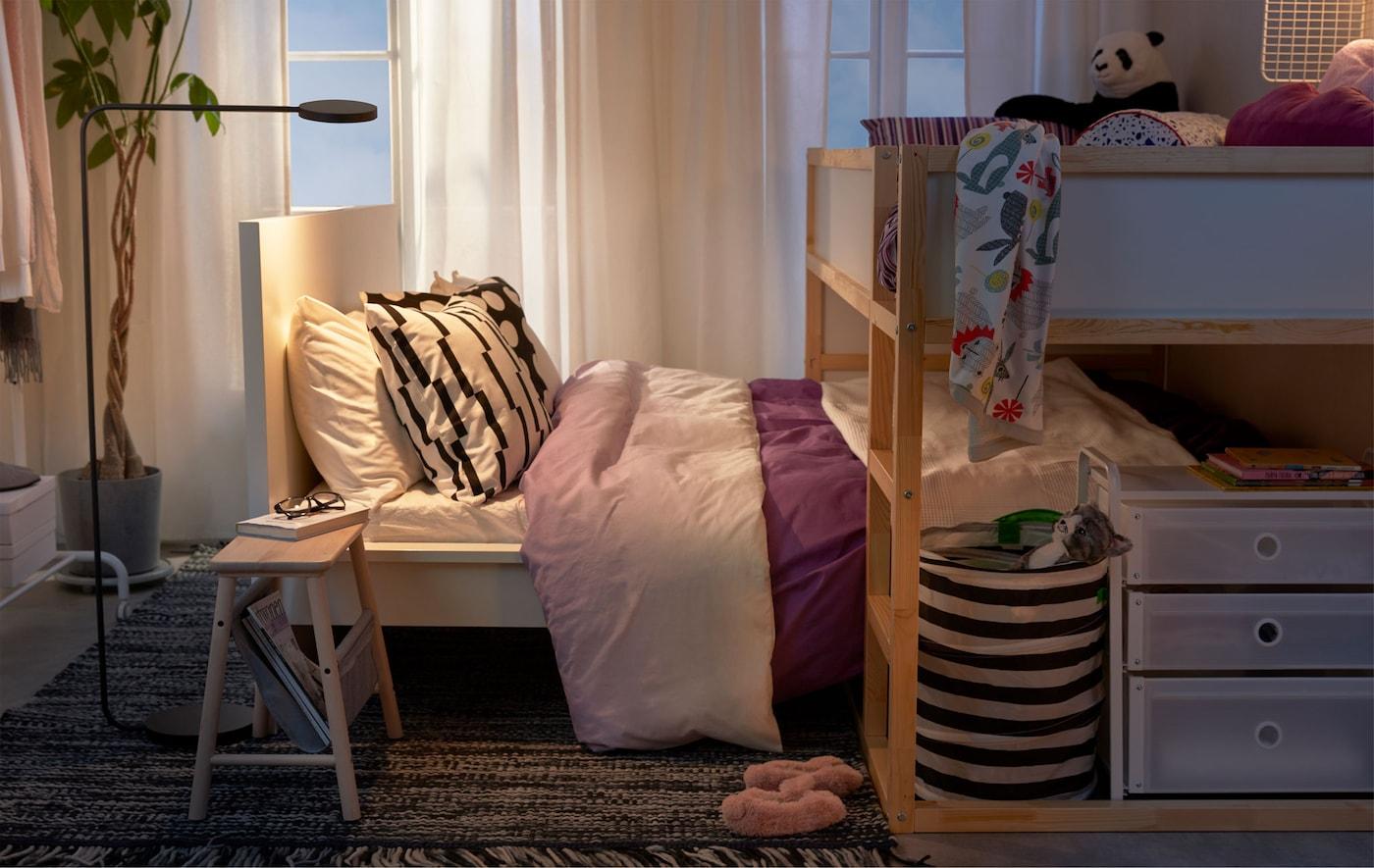 Cama alta colocada sobre uma cama mais baixa, como uma cama de criança encaixada na dos pais, num quarto pequeno.