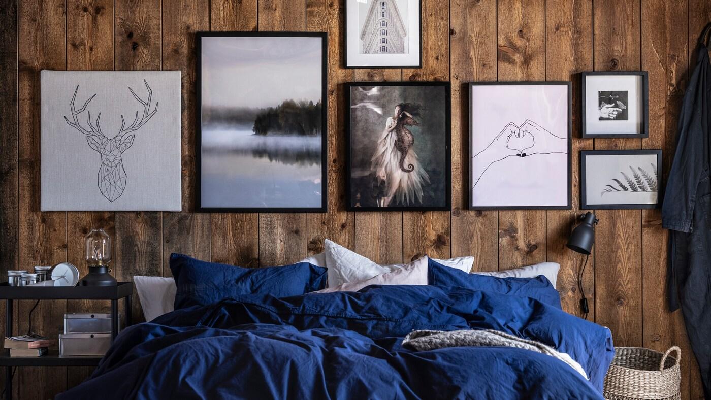 Cama com roupa de cama em azul/branco em frente a paredes de madeira decoradas com várias imagens em tons de preto, branco e cinzento.