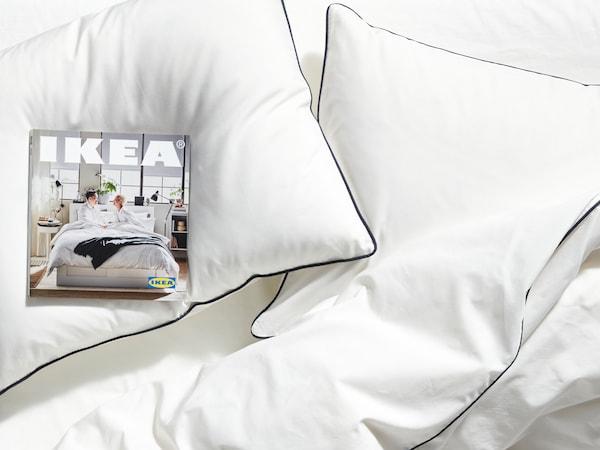 Cama con almohadas y edredón de color blanco, y una copia del Catálogo IKEA2020 encima de una de las almohadas.