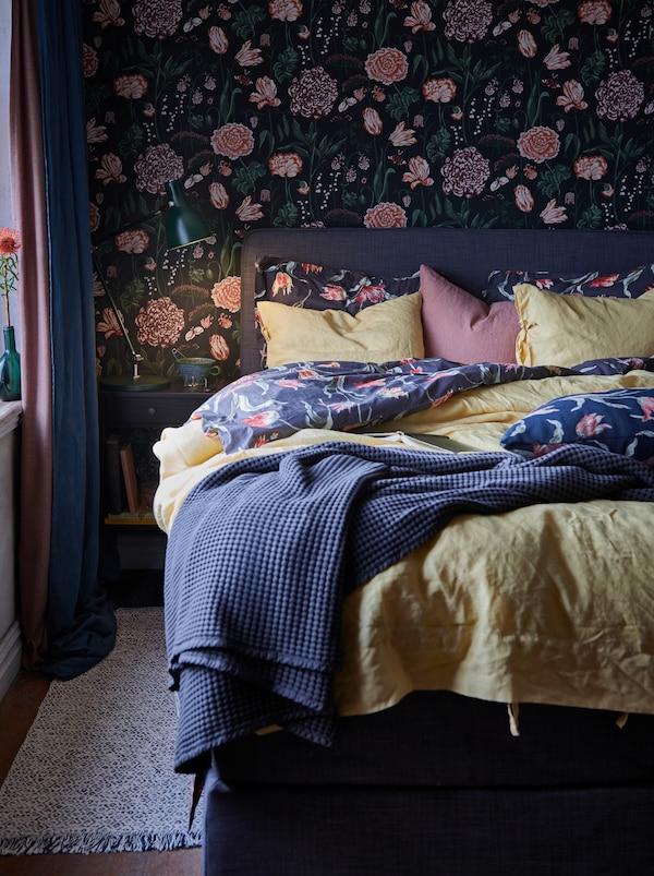 Cama con capas de edredones de estampado floral y una colcha gris. A su lado, hay una mesilla de noche con una luz de lectura.