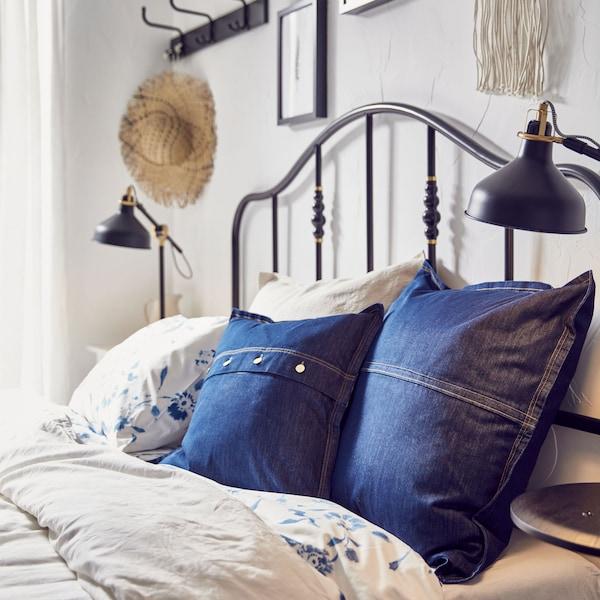 Cama con dos fundas de cojín IKEA SISSIL de tela vaquera azul entre otras almohadas.