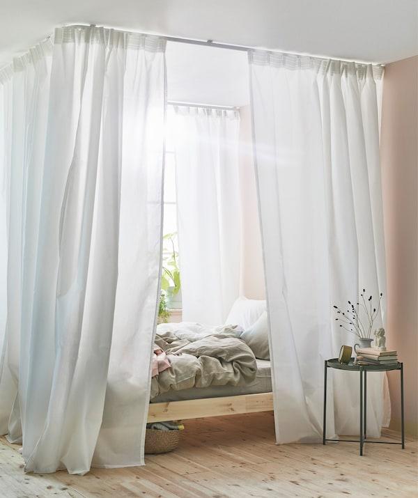 Cama con dosel con cortinas blancas utilizando un sistema de rieles VIDGA montados en el techo.