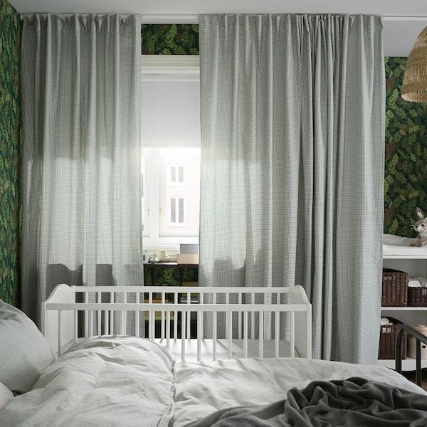 Cama e berce a carón dunha fiestra con cortinas verdes e brancas e un estor branco que non deixa pasar a luz cubrindo a parte superior.