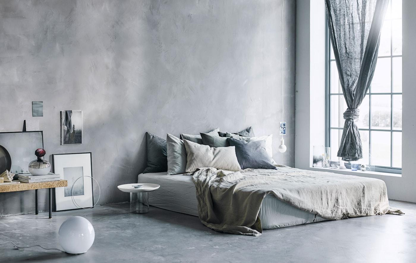 Cama grande con un montón de cojines y tejidos en tonos neutros en un dormitorio moderno y gris.