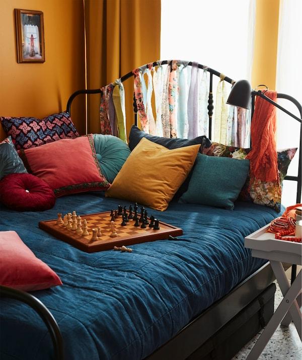 Cama grande e colorida com almofadas e um tabuleiro de xadrez em cima. Uma mesa-tabuleiro com bebidas colocada ao lado da cama.