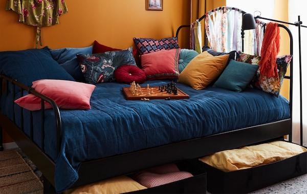 Cama grande e colorida com muitas almofadas e um tabuleiro de xadrez em cima. Roupa de cama guardada em caixas debaixo da cama.