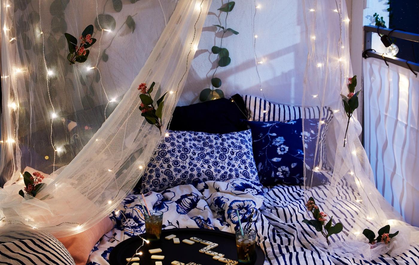 Cama larga numa varanda resguardada, com o mosquiteiro decorado com flores e iluminação LED, bebidas e peças de jogo num tabuleiro.