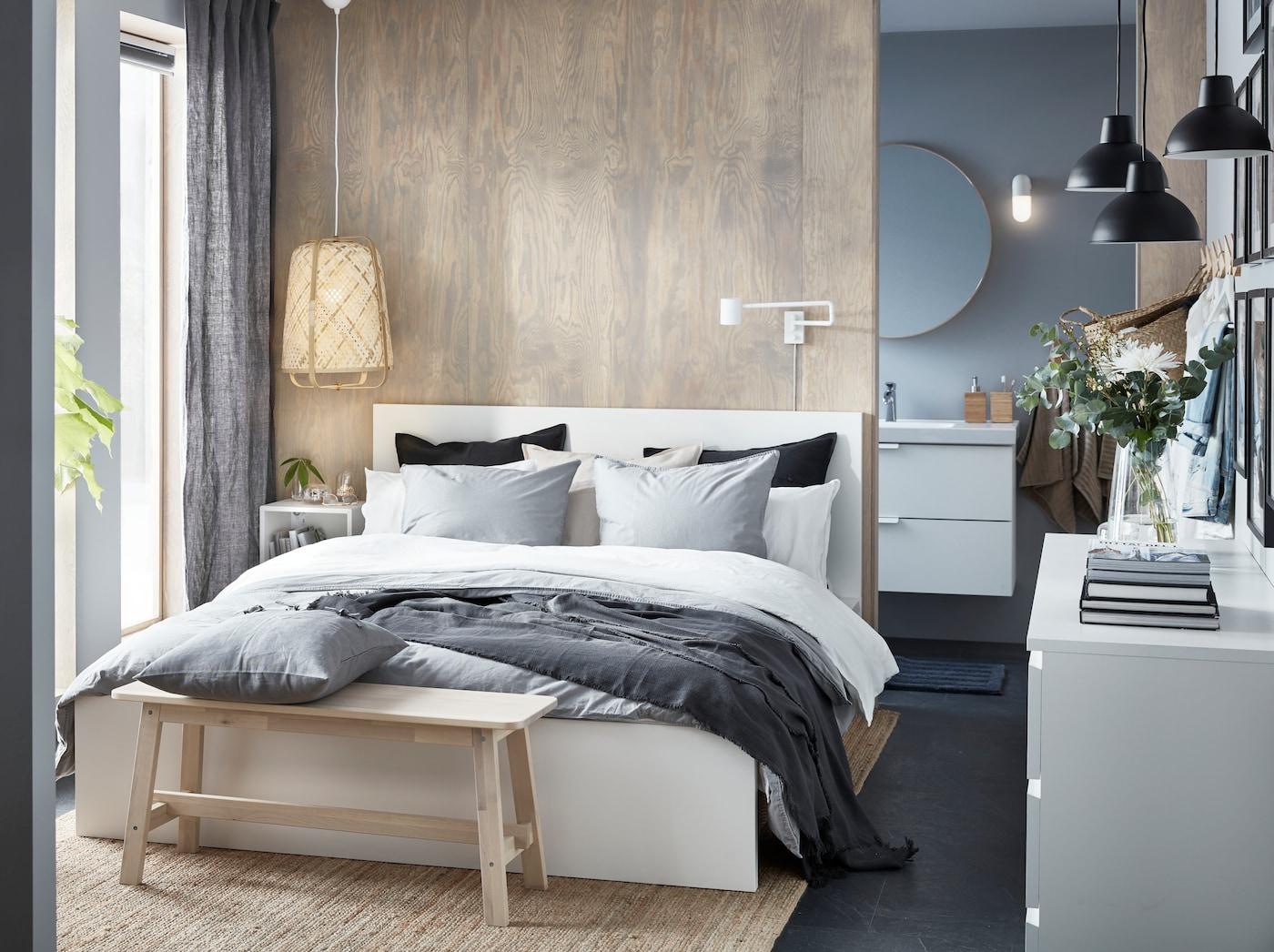 Cama MALM con ropa de cama blanca, gris claro y azul oscuro con un respaldo de madera y un banquito del mismo material.