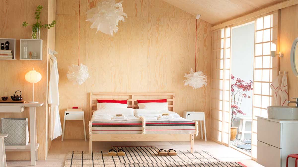 Camera con letto matrimoniale in pino massiccio grezzo, biancheria da letto bianca e rossa, e comodini bianchi – IKEA