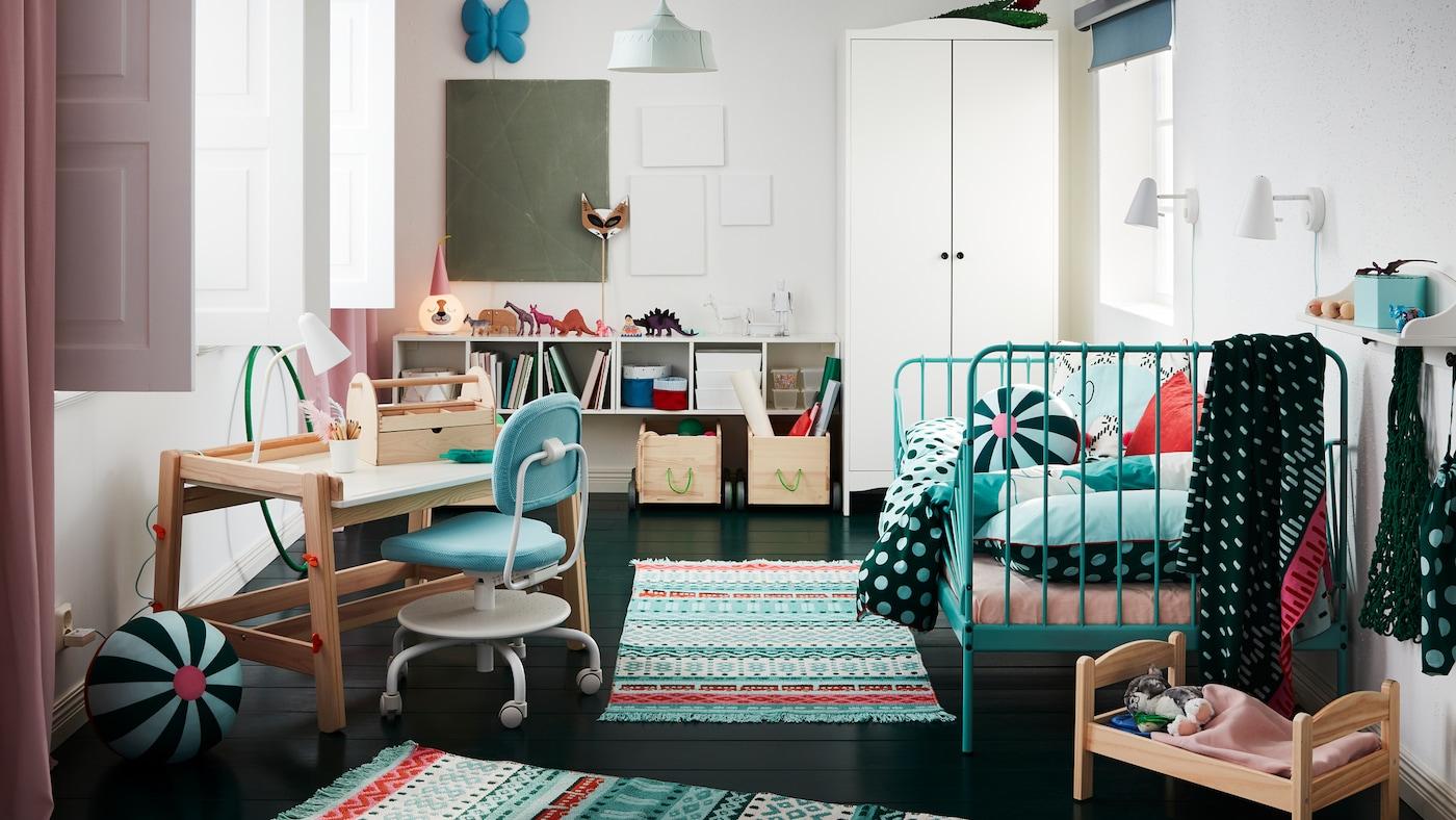 Camera copiilor, în care se află covoare pline de culoare, un cadru de pat turcoaz, un dulap de haine alb, un pat pentru păpuși și un birou pentru copii.