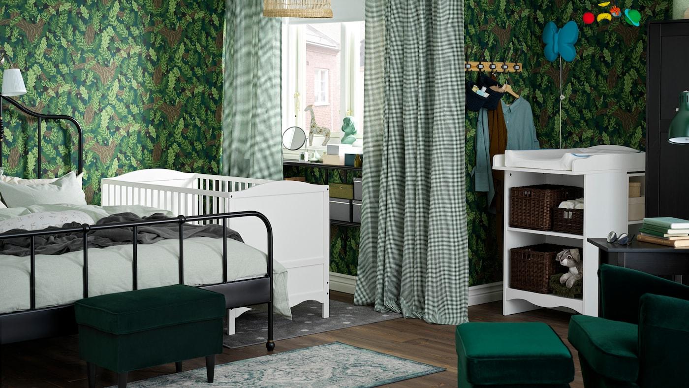 Camera copiilor verde, cu o masă de înfășat și un pătuț albe, un cadru de pat negru și draperii albe/verzi.