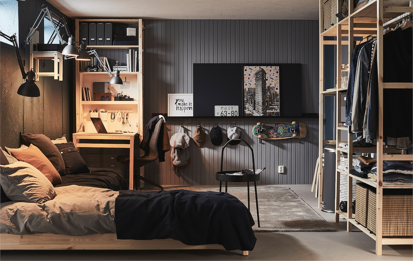 Camera da letto completamente arredata con finestre alte, come un garage o un seminterrato, con un letto, una scrivania e vari scaffali - IKEA
