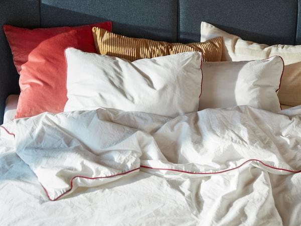 Camera da letto con divano letto di colore rosa-marrone chiaro, copripiumino giallo e federe.