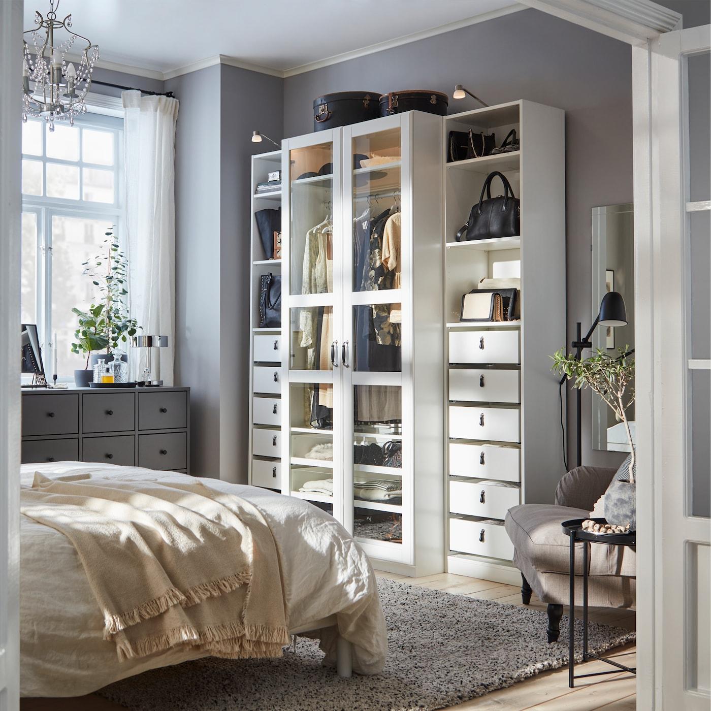 Camera da letto con guardaroba bianco con ante a vetro, cassettiera grigio scuro e poltrona grigio-beige – IKEA