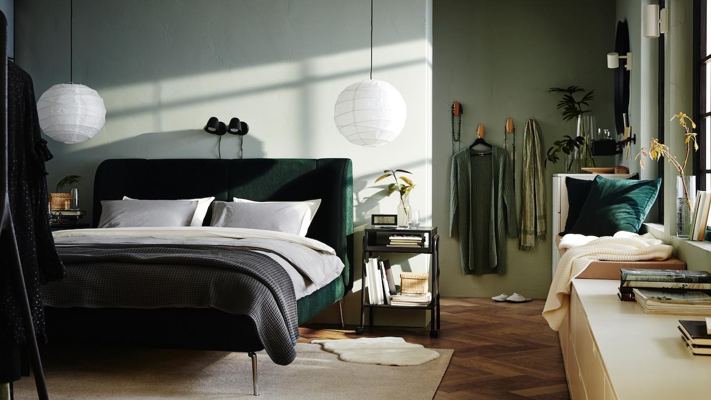 Camera da letto con letto TUFJORD verde, paralumi REGOLIT e cassettiere NORDLI con libri accanto alle finestre.