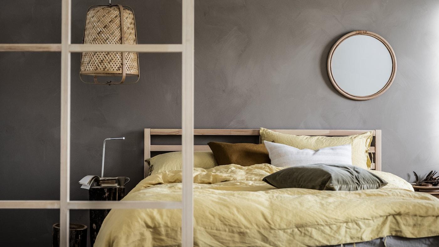 Camera da letto minimalista con pareti grigie e colori neutri, dettagli in legno, struttura letto matrimoniale TARVA e lampada KNIXHULT.