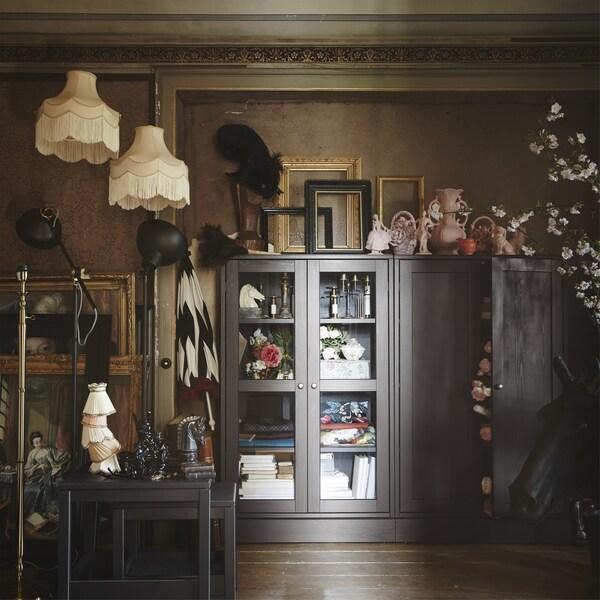 Cameră de zi cu abajururi, rame și un dulap cu ușă din sticlă.