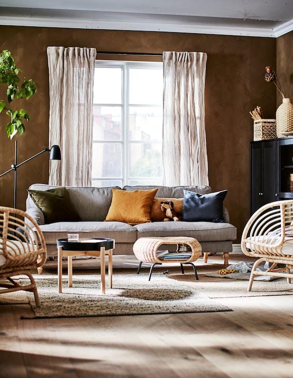 Cameră de zi cu schemă cromatică în culorile pământului, cu decorațiuni, corpuri de depozitare, scaune, măsuță de cafea, un taburet cu spațiu de depozitare și o plantă.