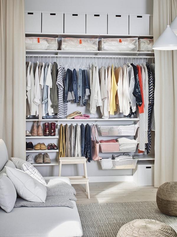 Camera de zi unde un perete este amenajat cu perdele până la podea trase care dezvăluie o garderobă organizată de-a lungul întregului perete.
