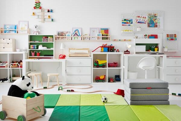 Camera pentru copii cu jucării pe pardoseală, birouri de-a lungul unei laturi și desene pe panouri perforat și polițe pentru fotografii FLISAT suspendate pe pereți.