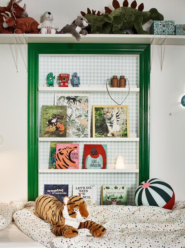 Cameretta con letto e parete bianca e verde. Peluche su una mensola e libri su mensole per quadri MOSSLANDA.