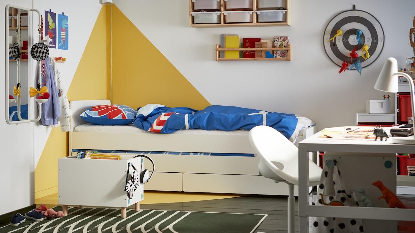 Cameretta con pareti bianche e disegno grafico giallo, struttura letto bianca con contenitori e biancheria da letto rossa e blu.