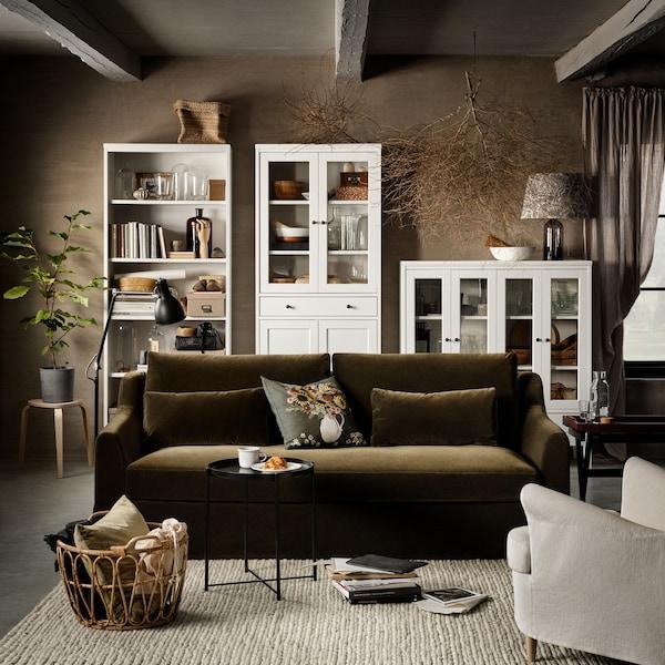 Canapé 2 places vert olive, armoire haute blanche avec portes vitrées et 1 tiroir, bibliothèque blanche et tabouret en bouleau.