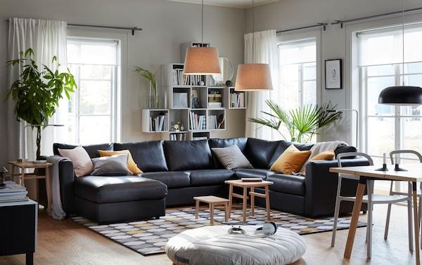Canapé d'angle 5 places VIMLE avec méridienne au milieu d'un salon chaleureux et gris.