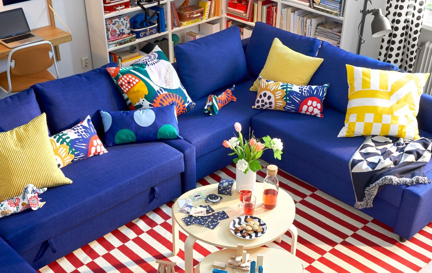 Canapé d'angle bleu avec coussins multicolores, deux tables basses circulaires et un tapis à rayures.