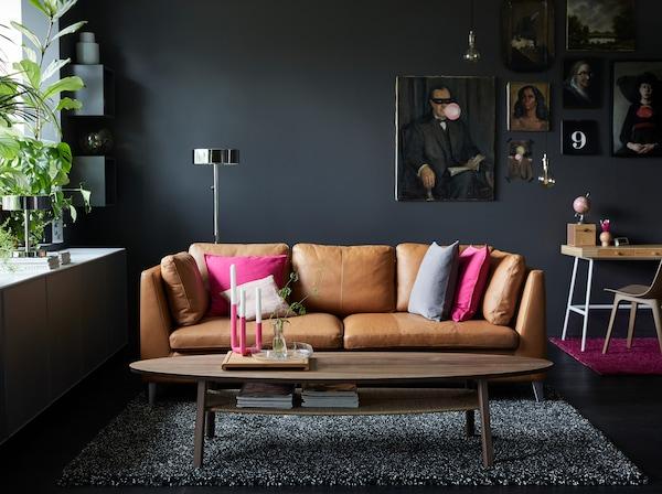 Canapé en cuir naturel avec des coussins rose et gris dans un salon aux murs gris foncé.