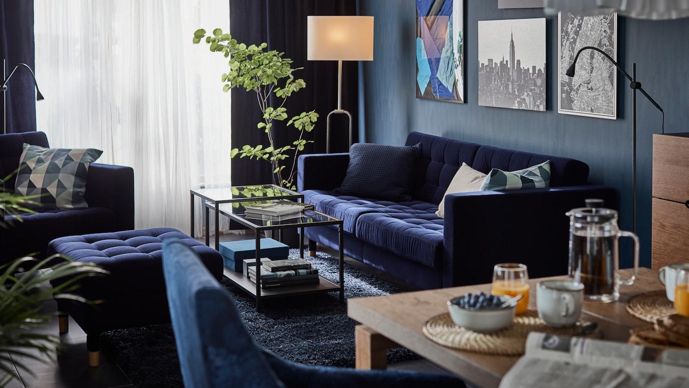 Canapé et repose-pieds LANDSKRONA bleus autour de deux tables d'appoint en verre, devant un mur orné d'images et à côté d'une plante.
