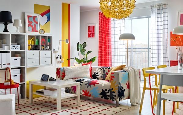 Canapé KLIPPAN couvert d'une housse multicolore audacieuse, étagères KALLAX blanches et table basse LACK dans une pièce lumineuse au style contemporain.