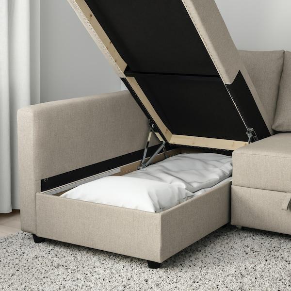Canapé-lit beige déplié avec vue sur la couette et les draps.