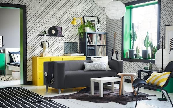 Canapé noir et blanc avec un motif à feuillage au milieu d'un salon noir, vert et jaune avec du papier peint à rayures diagolanes.