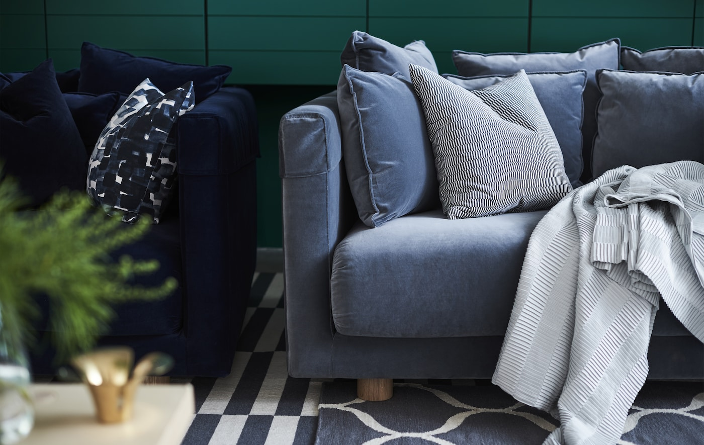 Canapé STOCKHOLM 2017 en velours bleu, avec coussins et plaids.