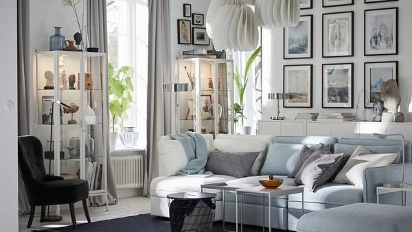 Canapeaua modulară, cu trei locuri, albastru deschis și o canapea modulară cu trei locuri, albă, de la IKEA, în camera de zi.