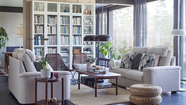 Canapele cu două locuri LIDHULT IKEA bej și bibliotecă BILLY albă cu polițe din sticlă într-un spațiu de cameră de zi.